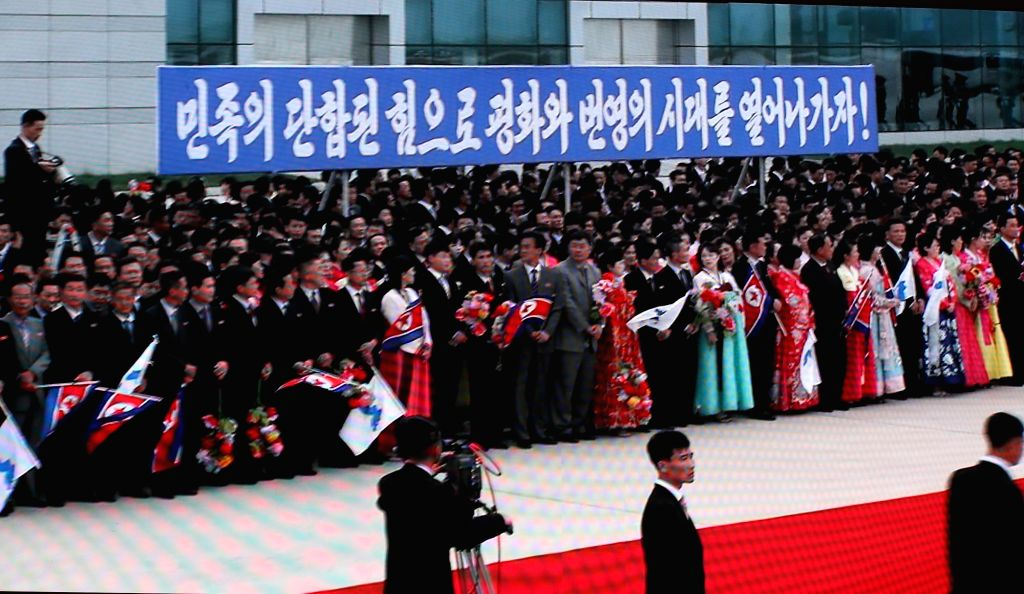 North Koreans are gathered at Pyongyang International Airport on Sept. 18, 2018, to welcome South Korean President Moon Jae-in in this TV live coverage shown at the main press center in Seoul. ...