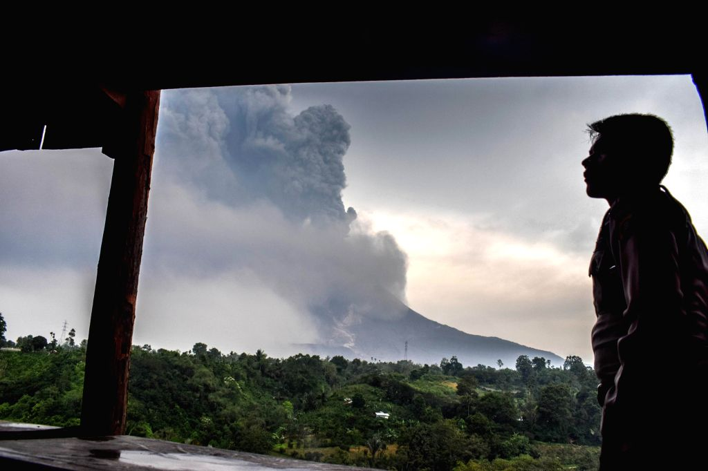 NORTH SUMATERA, April 7, 2018 - A man watches Mount Sinabung volcano spewing thick volcanic ash, seen from the town of Karo, North Sumatera, Indonesia, on April 6, 2018.