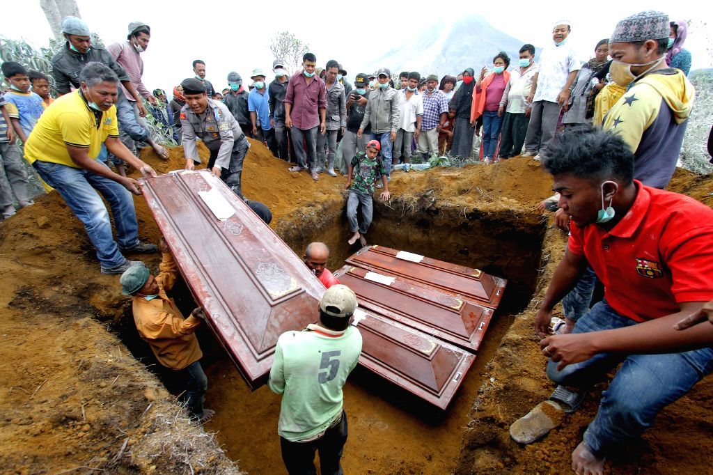 NORTH SUMATRA, May 22, 2016 - People put coffins into a mass grave during a funeral ceremony for victims in Mount Sinabung eruption at Sukandebi village in Karo, North Sumatra, Indonesia, May 22, ...