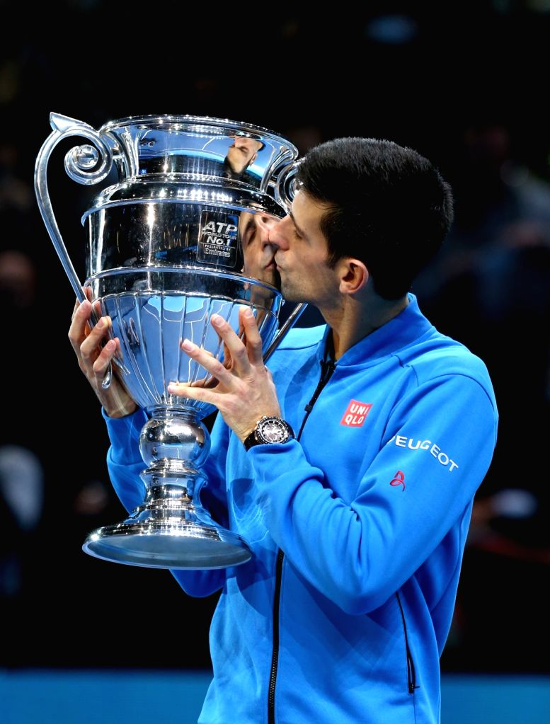 Novak Djokovic of Serbia kisses the ATP World No. 1 Award trophy following his men's singles group stage match against Kei Nishikori of Japan at the ATP World Tour ...