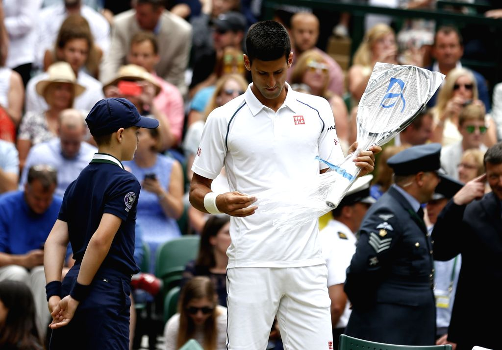Novak Djokovic of Serbia takes out a new racket during men's singles final against Roger Federer of Switzerland at the 2015 Wimbledon Championships in Wimbledon, ...