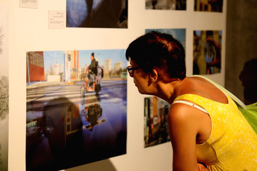 """NOVI SAD, July 22, 2019 - A visitor views photos during the photo exhibition """"Reflection in Water"""" in Novi Sad, Serbia, July 21, 2019. The changes in urban and rural China were presented to ..."""