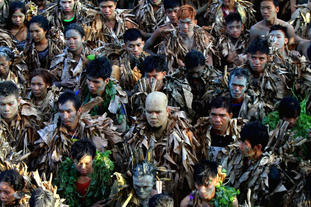 Devotees covered with mud and banana leaves attend a mass during the annual Taong Putik (Mud People) Festival in Nueva Ecija Province, the Philippines,
