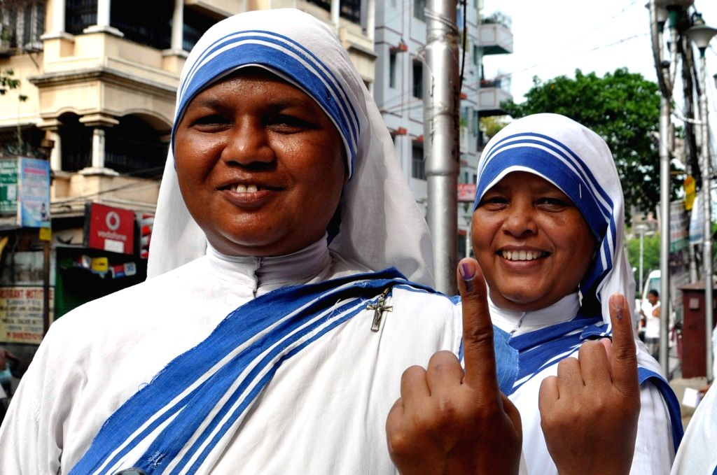 Nuns shows their forefingers marked with phosphorus ink after casting her vote at the polling station during the West Bengal Assembly Election in Kolkata on April 21, 2016.