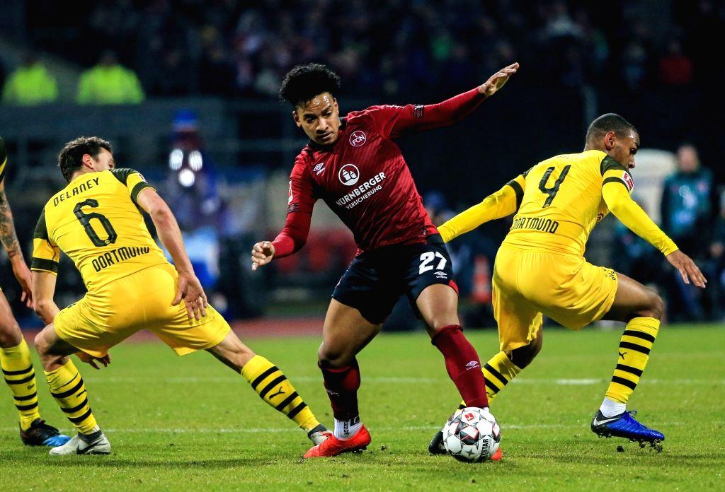 NUREMBERG, Feb. 19, 2019 - Nuremberg's Matheus Pereira (C) breaks through the defense from Dortmund's Thomas Delaney (L) and Abdou Diallo during a German Bundesliga match between 1. FC Nuremberg and ...