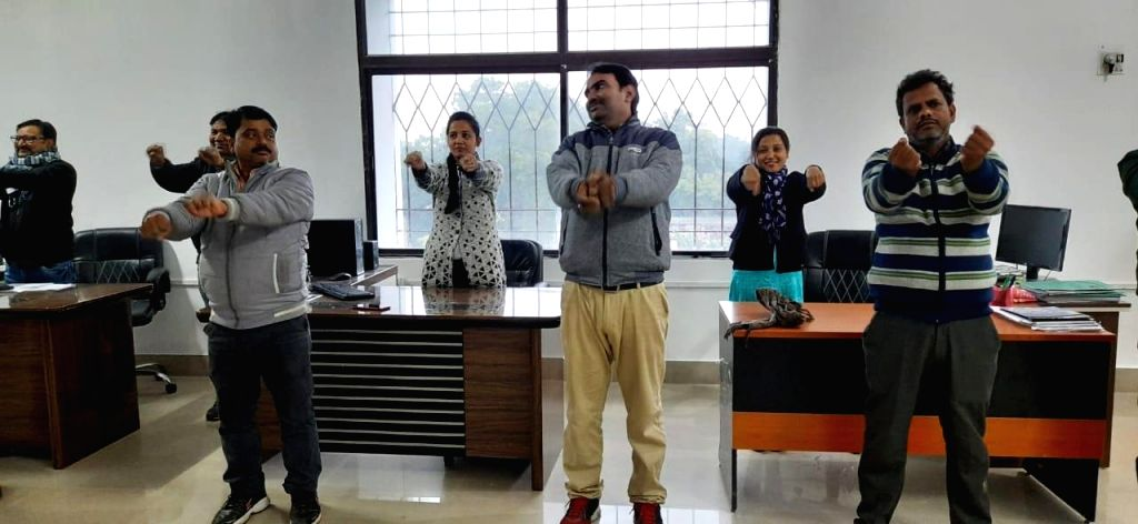 Officers and employees practice yoga in office.