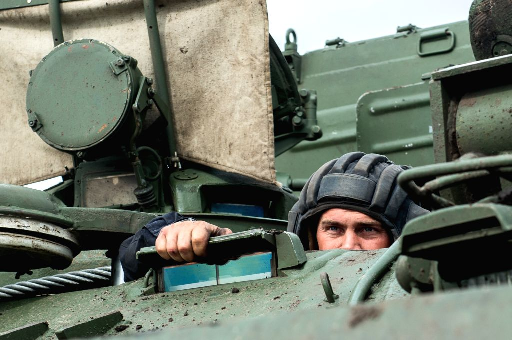 """OMSK, Aug. 10, 2017 - A Russian tank crew member looks out of the tank during the """"Maintenance battalion"""" of International Army Games 2017 contest in Omsk region, Russia, on Aug. 9, 2017. ..."""