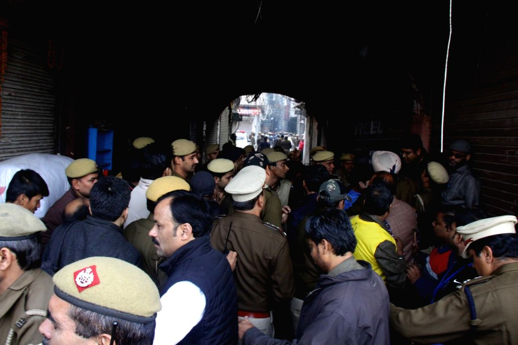 Onlookers with police personnel at the area of a fire incident in which 43 people died in  West Delhi's Rani Jhansi Road area on Dec. 8, 2019.