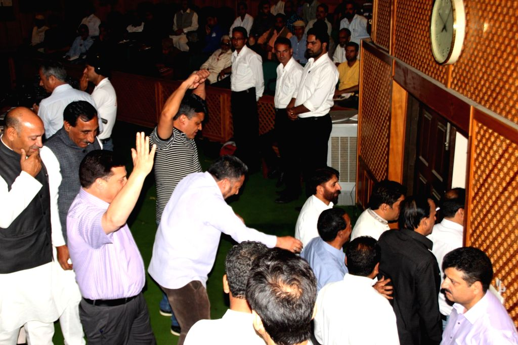 Opposition legislators in Jammu and Kashmir assembly walk out of the assembly during budget session in Srinagar on June 2, 2016.