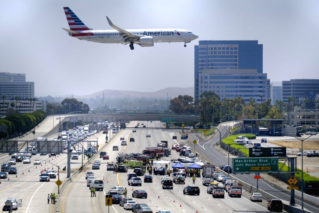ORANGE COUNTY (U.S.), June 30, 2017 An aircraft flies over the site where a small plane crashed in Orange County, California, the United States, on June 30, 2017. A twin-engine airplane ...