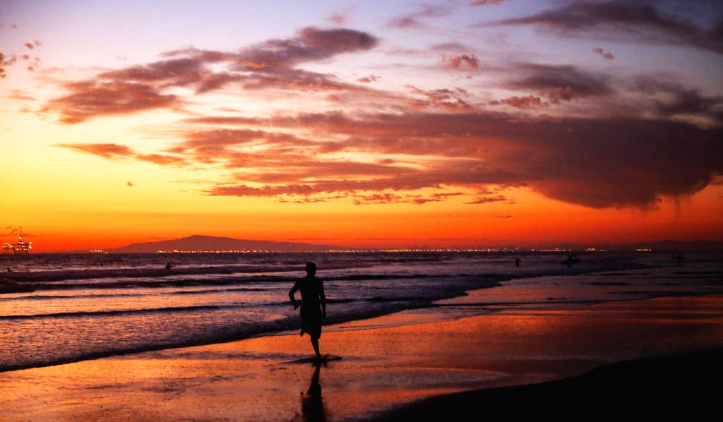 ORANGE COUNTY (U.S.), Nov. 3, 2019 A man is silhouetted against sunset on the Huntington Beach, California, the United States, on Nov. 2, 2019.