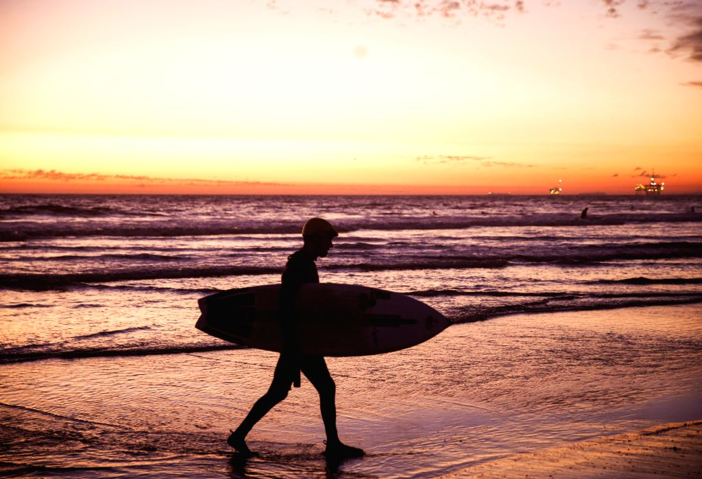 ORANGE COUNTY (U.S.), Nov. 3, 2019 A surfer is silhouetted against sunset on the Huntington Beach, California, the United States, on Nov. 2, 2019.