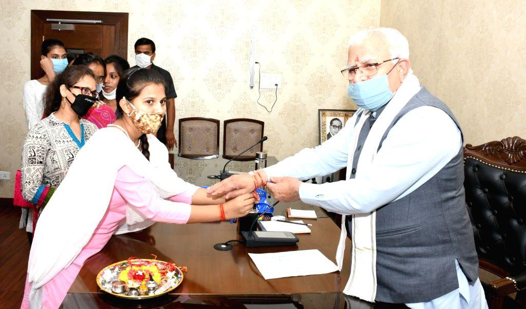 Orphan girls tie rakhis on the wrist of Haryana Chief Minister Manohar Lal Khattar on the eve of Rasha Bandhan in Chandigarh on Aug 2, 2020. - Manohar Lal Khattar