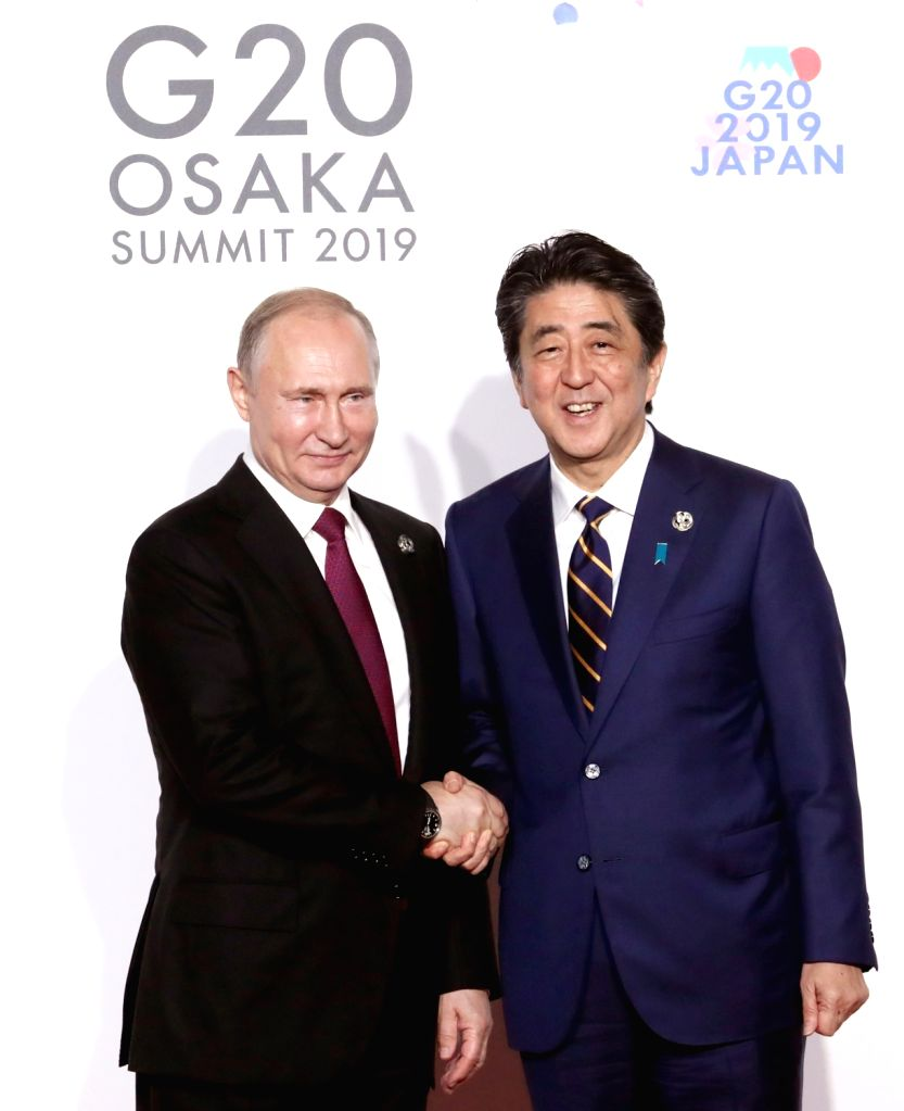 Osaka: Russian President Vladimir Putin (L) and Japanese Prime Minister Shinzo Abe pose for a photo during a welcome ceremony for a Group of 20 summit in Osaka, Japan, on June 28, 2019. (Yonhap/IANS) - Shinzo Abe