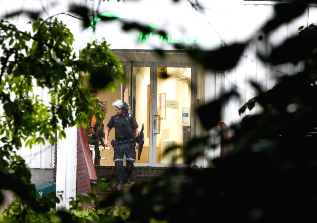 OSLO, Aug. 10, 2019 - A police officer walks out of the Al-Noor Islamic Center after a shooting in Baerum, near Oslo, Norway, on Aug. 10, 2019. A dead person was found after the Mosque shooting ...
