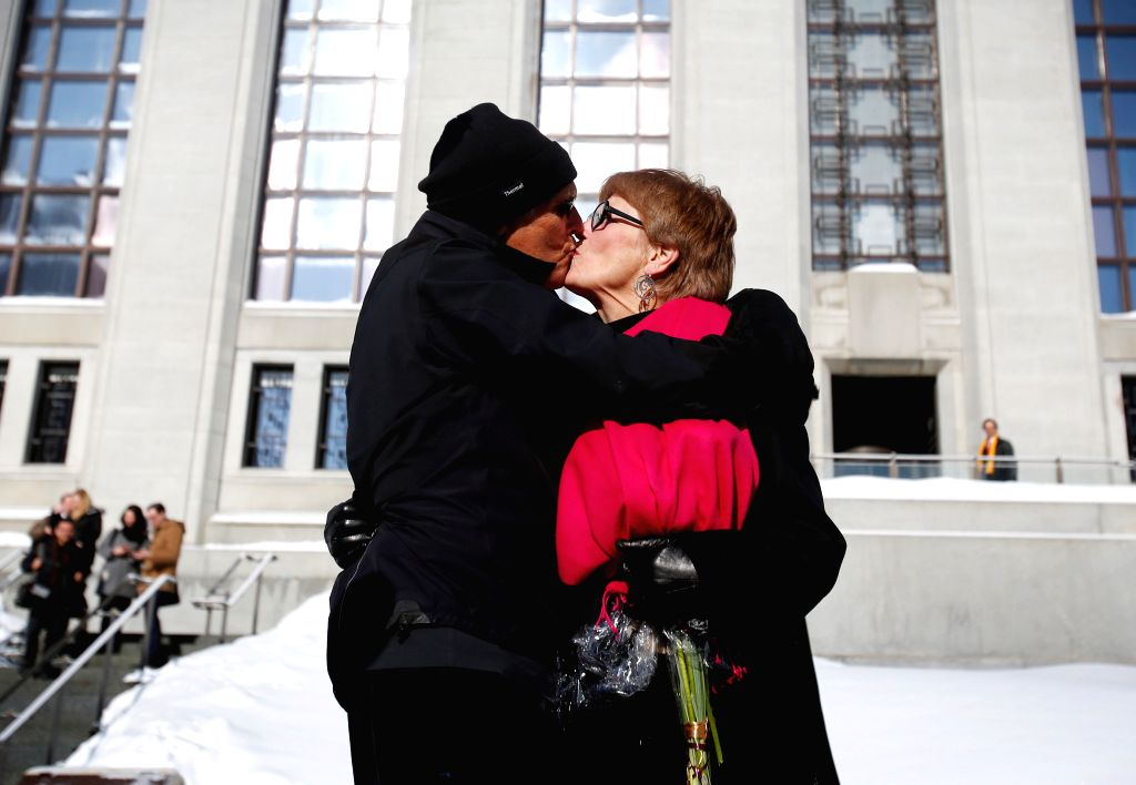 Lee Carter (R) kisses her husband Hollis Johnson in front of the Supreme Court of Canada after the Court struck down laws prohibiting assisted suicide in Canada, in ..