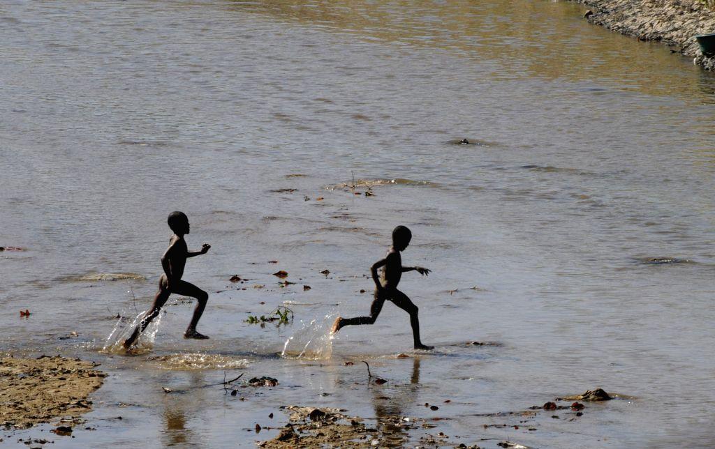 Haitian boys play in the Masacre river in Ouanaminthe city, Haiti, on Jan. 12, 2015. A 7.3-magnitude earthquake struck Haiti on Jan. 12, 2010, killing at least .