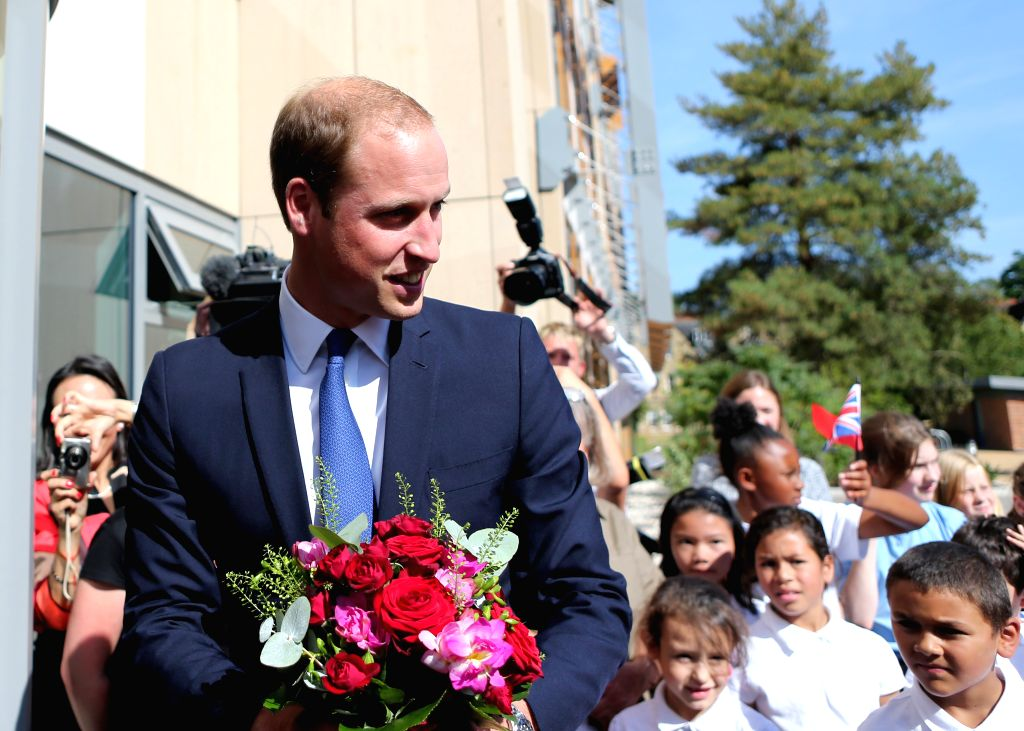 Prince William (R), Duke of Cambridge, receives flowers for his wife Catherine, Duchess of Cambridge, as he arrives to formally inaugurate the Dickson Poon ...