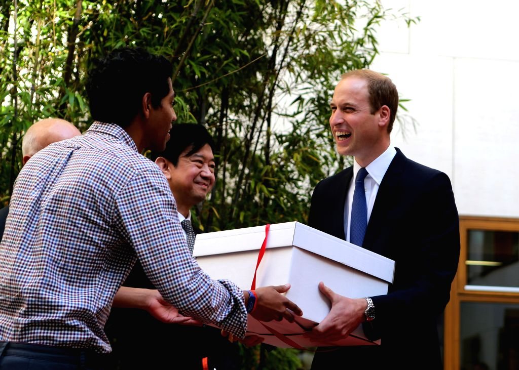 Prince William (R), Duke of Cambridge, receives gifts during the unveiling of the Dickson Poon University of Oxford China Centre Building in Oxford, the United ...
