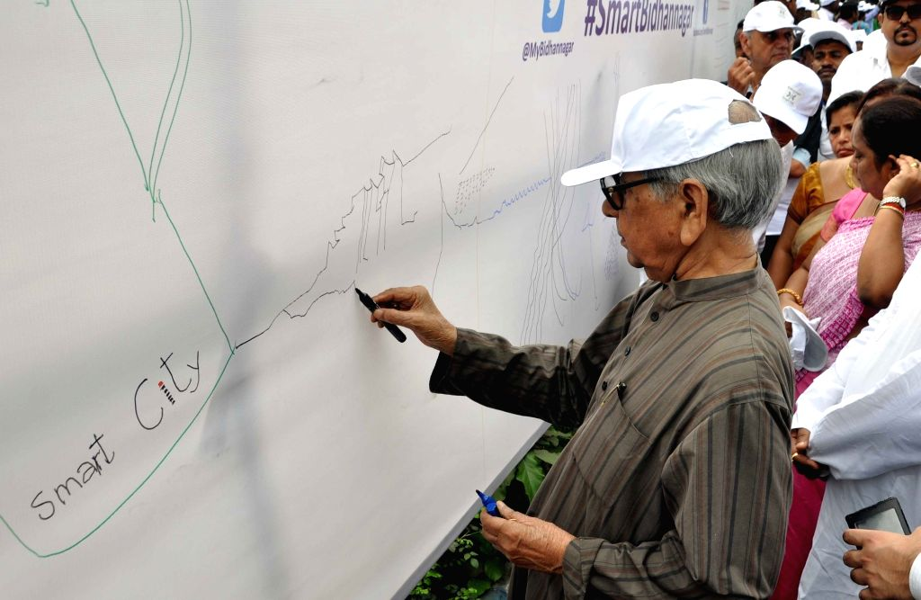 Painter Ganesh Haloi paints on a canvas for support of `Smart Bidhannagar` in Kolkata on Oct 31, 2015.