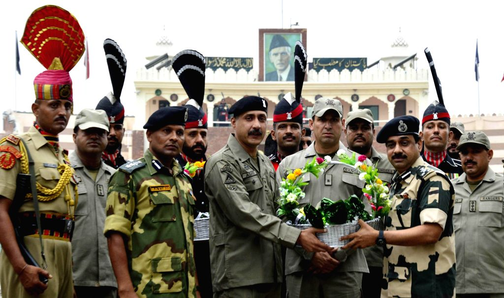 Pak Rangers officials giving sweets and fruit basket to his Indian counterparts at Attari land border on the occasion of Eid ul Fitr on July 29, 2014.