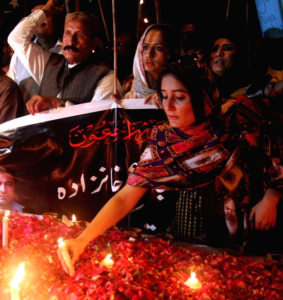 Pakistani civil society members light candles during a vigil ceremony to pay tribute to Punjab home minister Shuja Khanzada in southern Pakistani port city of ... - Shuja Khanzada