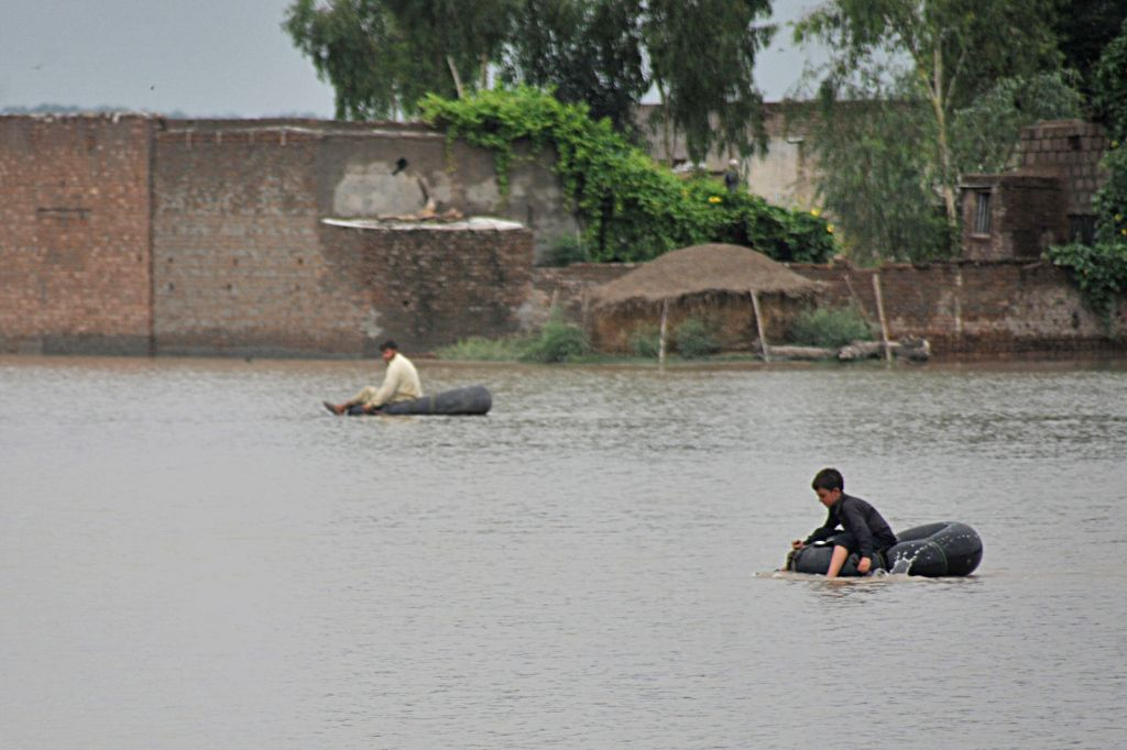 Pakistani flood-affected people go across floodwater with rafts on the outskirts of Peshawar, northwest Pakistan, on Aug. 3, 2015.