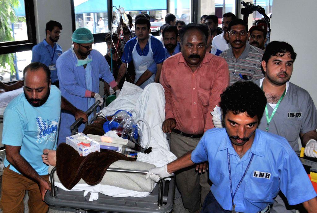 Pakistani paramedics transfer critically injured Muttahida Qaumi Movement (MQM) legislator Rashid Godil to a hospital after an attack by gunmen in southern ...