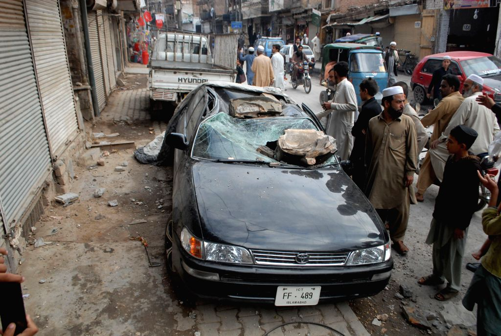 Pakistani people gather near a damaged car after a severe earthquake in northwest Pakistan's Peshawar, Oct. 26, 2015. At least 64 people were killed and over 400 ...