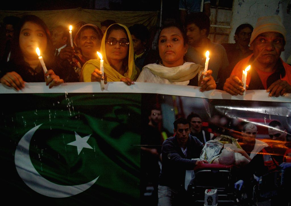 Pakistani people hold candles during a vigil ceremony for the victims of Paris terror attacks in eastern Pakistan's Lahore, Nov. 16, 2015.