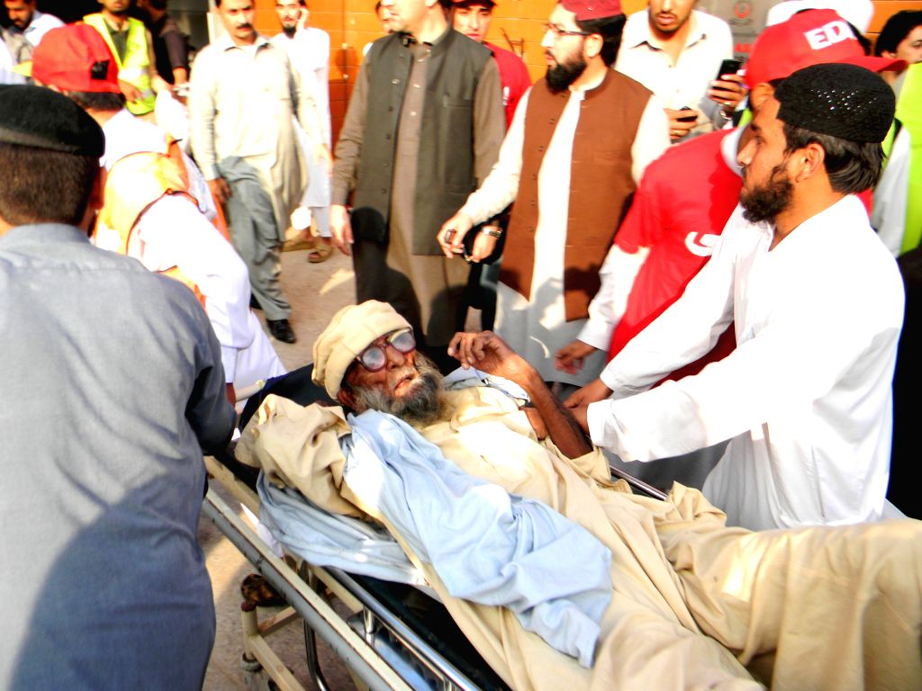 Pakistani people transfer an injured man to a hospital after a severe earthquake in northwest Pakistan's Peshawar on Oct. 26, 2015. At least 125 people were killed ...