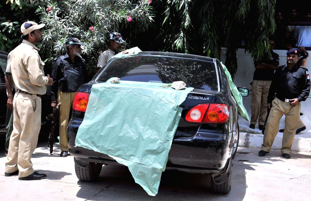 Pakistani policemen stand beside the vehicle used by Muttahida Qaumi Movement (MQM) opposition party legislator Rashid Godil following an attack by gunmen in ...