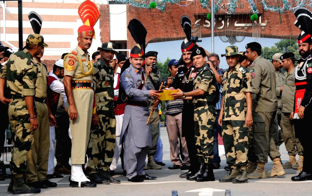 Pakistani Ranger sector Commander Shaukat Ali presents sweets to Border Security Force (BSF) Commandant Sudeep during a ceremony organised to celebrate Pakistan's Independence Day at ...