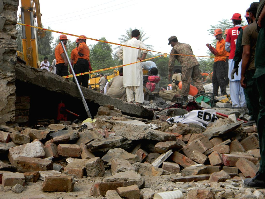 Pakistani rescuers search for victims at the blast site in east Pakistan's Attock on Aug. 16, 2015. At least 15 people were killed including the home minister of ...