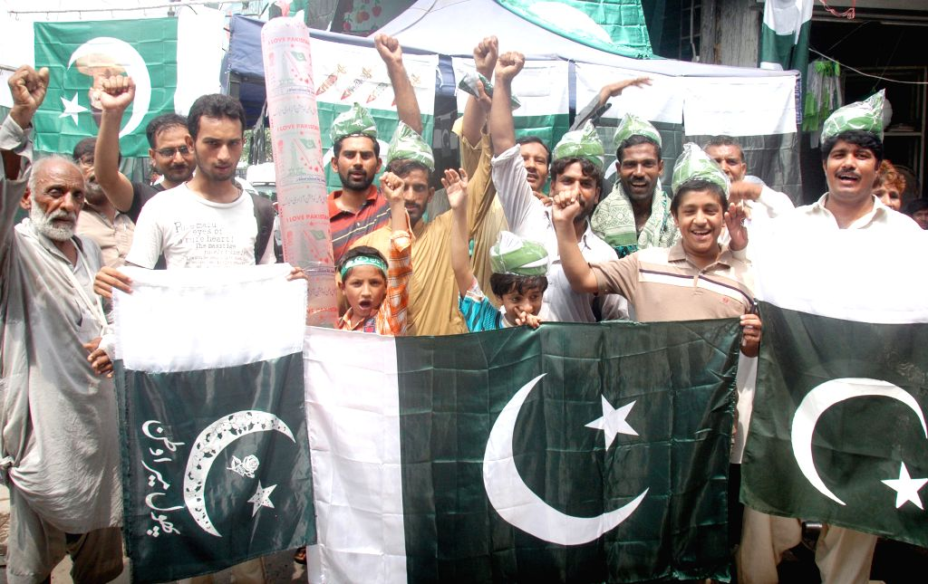 Pakistanis hold national flags on a street ahead of the country's Independence Day in Lahore, eastern Pakistan, Aug. 12, 2015. Pakistan will celebrate its ...