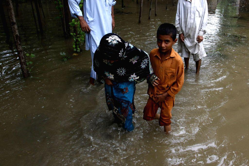 Pakistanis wade through floodwater on the outskirts of Peshawar, northwest Pakistan, on Aug. 3, 2015.