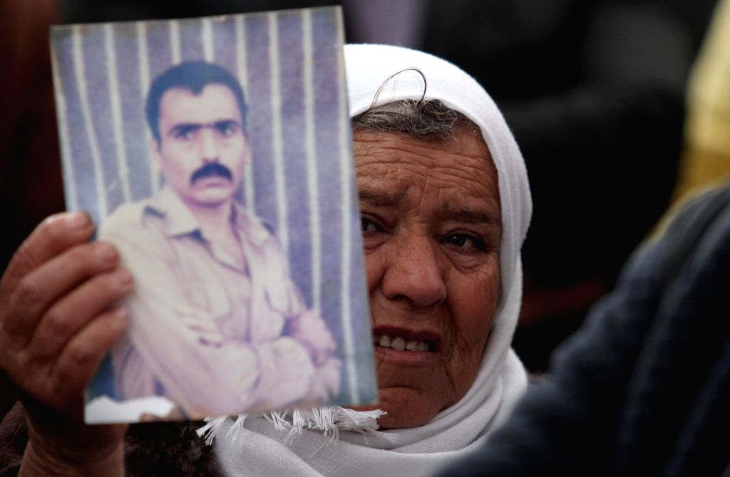 PALESTINE, Feb. 19, 2019 - A Palestinian holds a photo of her relative held in Israeli jails as she takes part in a protest against an Israeli decision to trim funds over prisoner stipends, in the ...