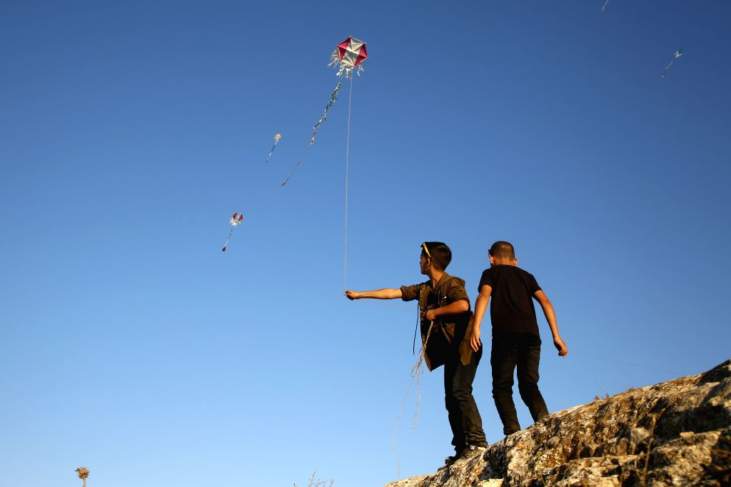Palestinian children fly kites during the Eid al-Adha holiday, in the West Bank city of Nablus, on August 1, 2020.