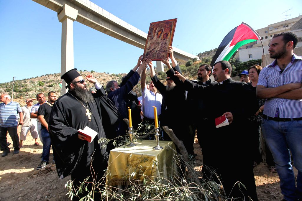 Palestinian Christians take part in a prayer near uprooted olive trees in the West Bank town of Beit Jala near the Jewish settlement of Gilo and adjacent to the ...
