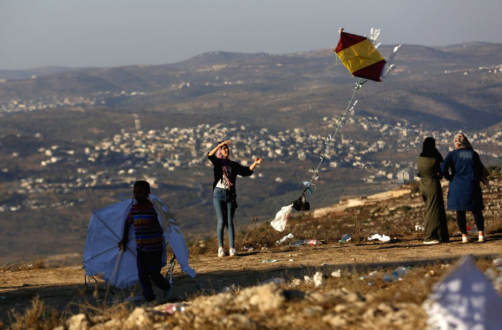 Palestinian people fly kites during the Eid al-Adha holiday, in the West Bank city of Nablus, on August 1, 2020.