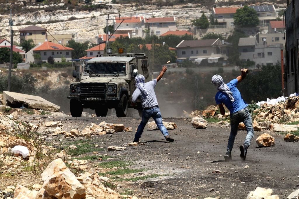 Palestinian protesters hurl stones at Israeli soldiers during clashes after a protest against the expanding of Jewish settlements in Kufr Qadoom village near the West Bank city of Nablus, on ...