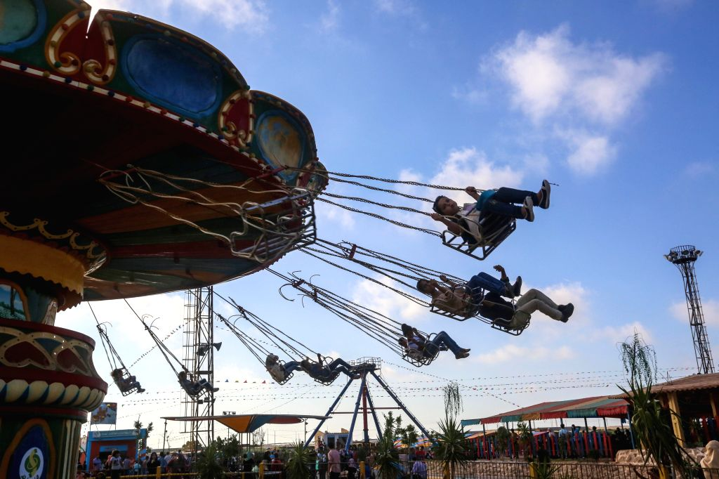 Palestinians enjoy their second day of Eid al-Fitr holidays in an amusement park in Gaza City on July 18, 2015. Muslims around the world are celebrating Eid al-Fitr, ...