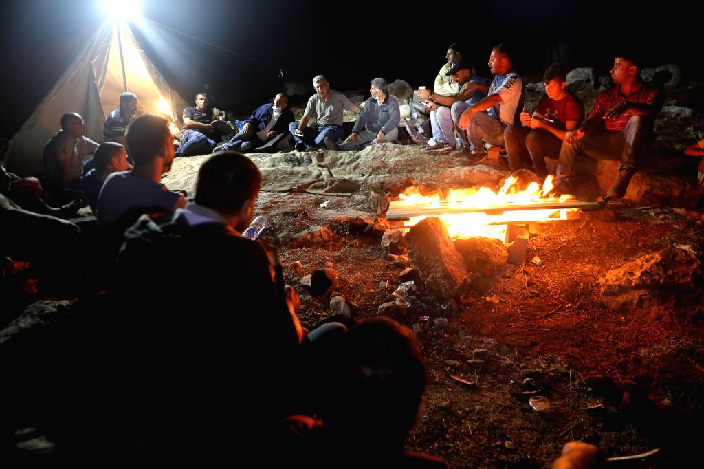 Palestinians gather to guard their lands in the West Bank village of Dura near Hebron, on Aug. 29, 2020. For seven days in a row, dozens of Palestinians from the ...