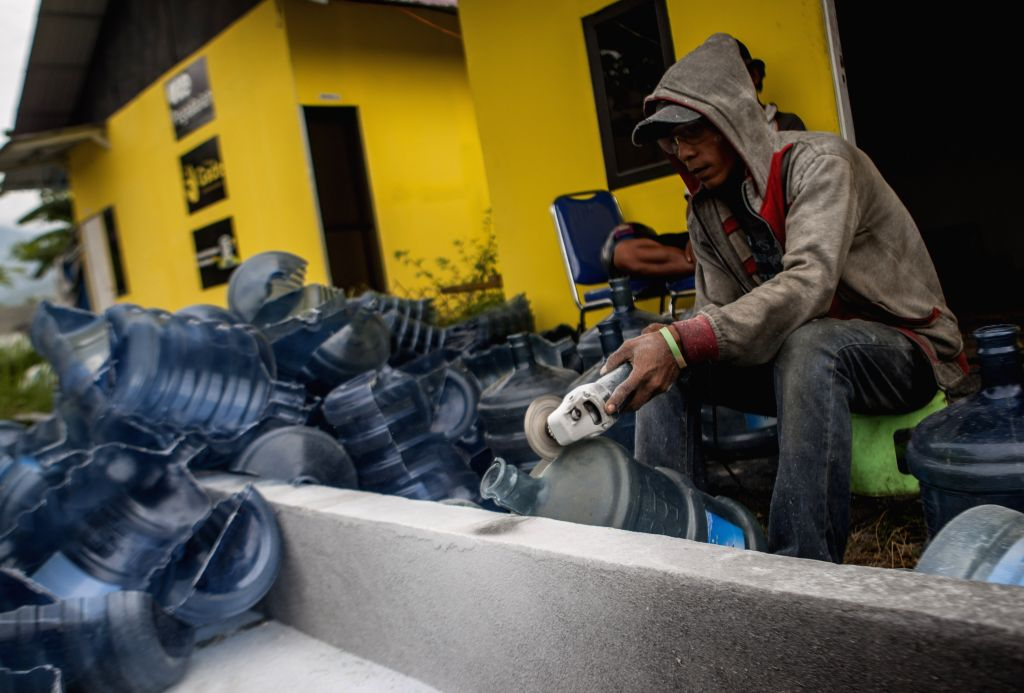 PALU, July 18, 2019 - A worker cuts a plastic water bottle to process it into small pieces for recycling in Palu, Central Sulawesi, Indonesia, July 18, 2019. Indonesia's plastic waste processing ...