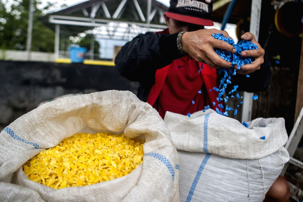 PALU, July 18, 2019 - A worker fills small pieces of processed plastic waste into sacks in Palu, Central Sulawesi, Indonesia, July 18, 2019. Indonesia's plastic waste processing industry not only ...