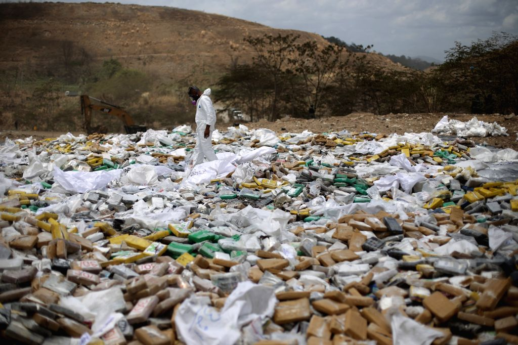 An element of the National Police destroys drug packs during a controlled burning of narcotics in the landfill of Cerro Patacon, in Panama City, capital of ...