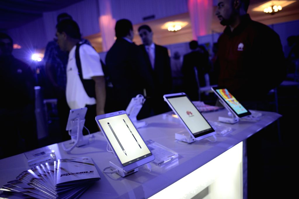 Visitors look at telecommunication products during Huawei's exhibition ICT in Panama City, capital of Panama, on July 29, 2014. International telecommunications