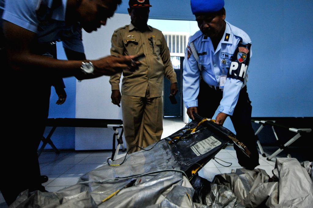 Officers take a photo of plastic for baggage that suspect as Air Asia QZ 8501 belonging that found on the sea of Karimata at Pangkalan Bun airport, Central ...