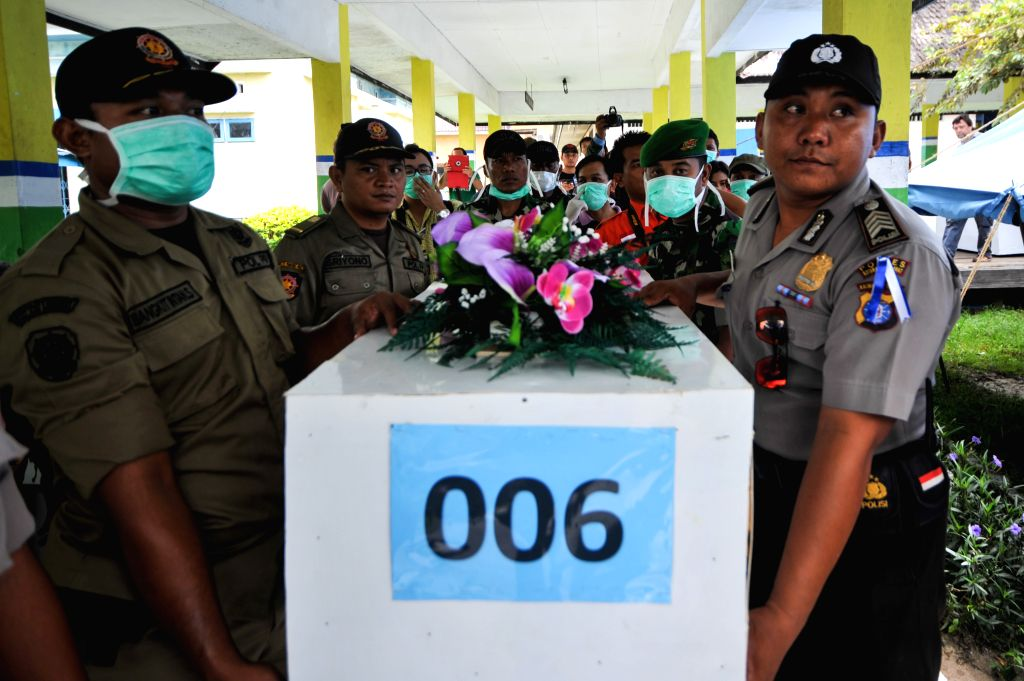 Officers bring the coffin that contains the sixth victim of AirAsia flight QZ8501 who has been cleaned to Iskandar Air Base in Pangkalan Bun, Central ...