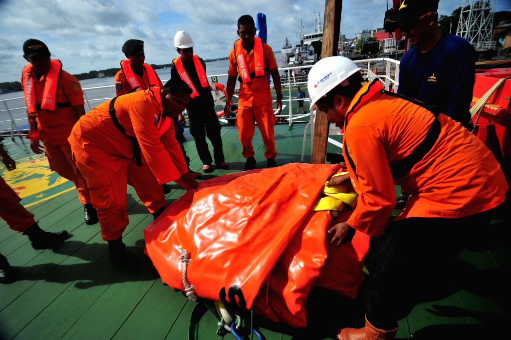 Members of Indonesian Navy and National Search and Rescue Agency load huge balloons to raise the tail of AirAsia plane to the rescue ship at Kumai port, ...